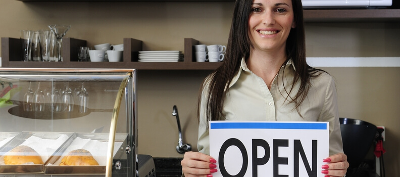 woman holding business open sign