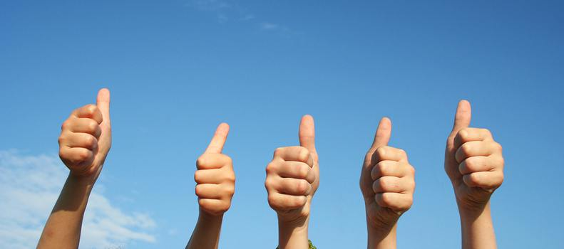 Five people holding the thumbs up sign with a blue sky in the background.